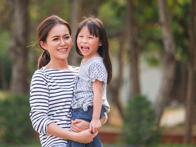 彼女の母親の腕の中で幸せな女の子の顔を閉じます。