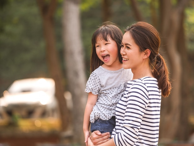 彼女の母親の腕の中で幸せな少女の顔を閉じます。