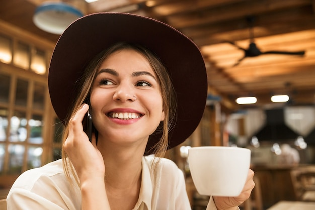 Close up of a happy lovely woman in hat sitting
