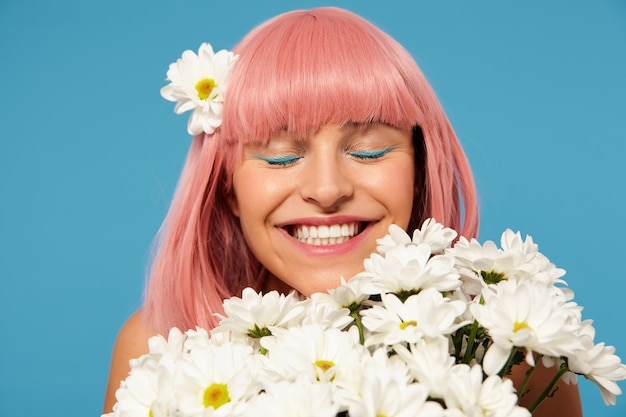 Close up of happy lovely young pink haired lady with bob haircut holding truss of flowers while standing over blue background, keeping eyes closed while smiling widely