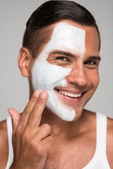 Uomo felice del primo piano che applica la maschera per il viso