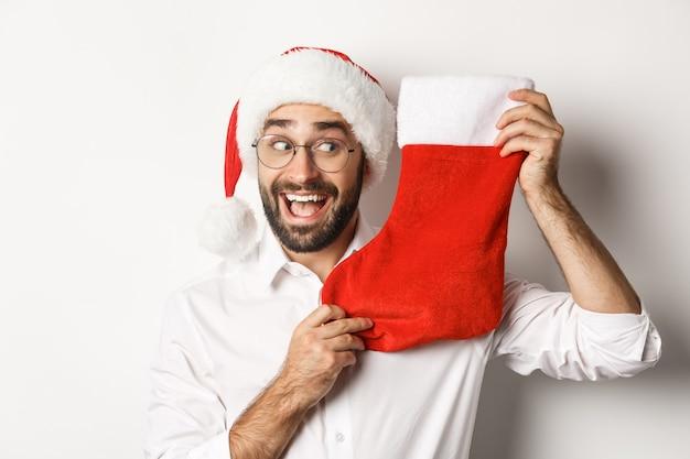 Primo piano di uomo felice che celebra il natale, riceve regali in calza di natale e sembra eccitato, indossando occhiali e cappello da babbo natale