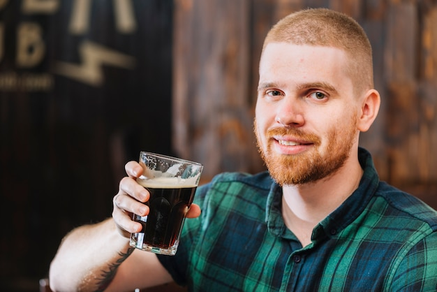 Close-up of a happy man drinking beer