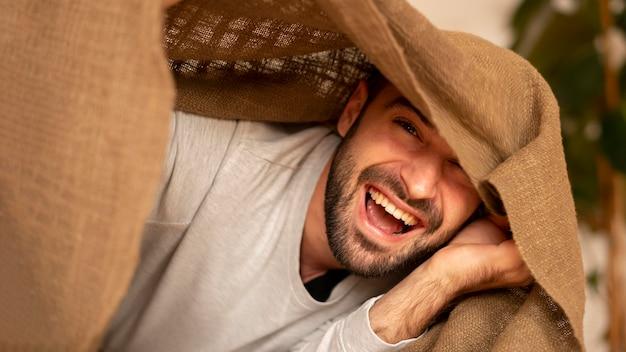 Крупным планом счастливый человек с одеялом