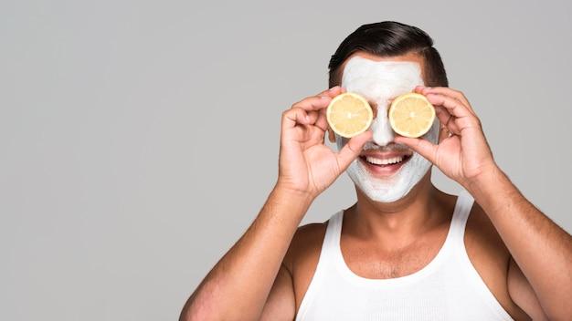 フェイスマスクとレモンのクローズアップの幸せな男