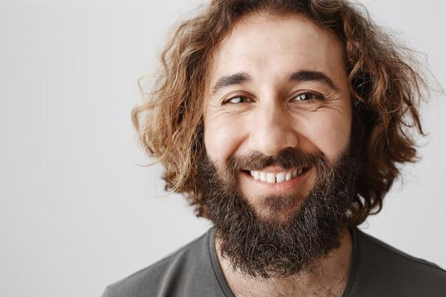 Primo piano di felice uomo mediorientale con barba lunga e taglio di capelli ricci sorridente gioioso