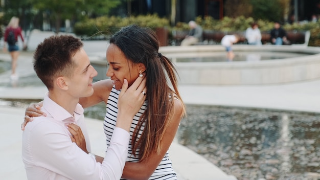 Close-up of happy mixed-race couple in love having date one summer day outdoors