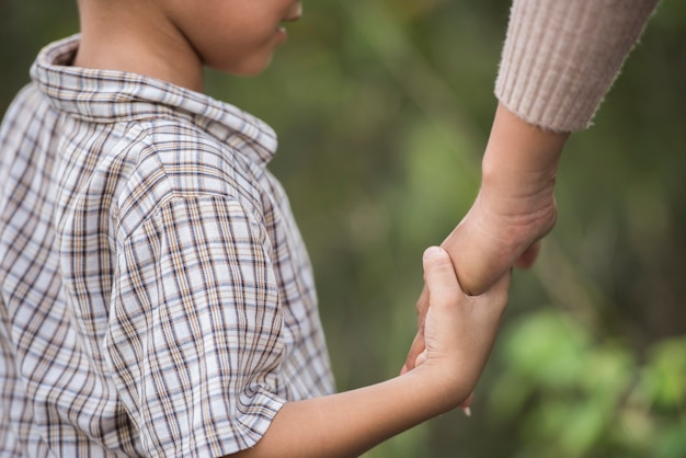 Chiuda su della mamma felice e del figlio che tengono la mano in un parco. concetto di famiglia