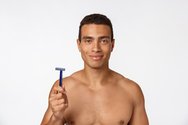 Close up of a happy naked african man holding razor isolated