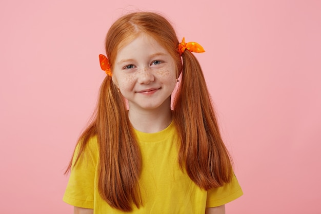 Close up of happy petite freckles red-haired girl with two tails, smiling and looks cute, wears in yellow t-shirt, stands over pink background.