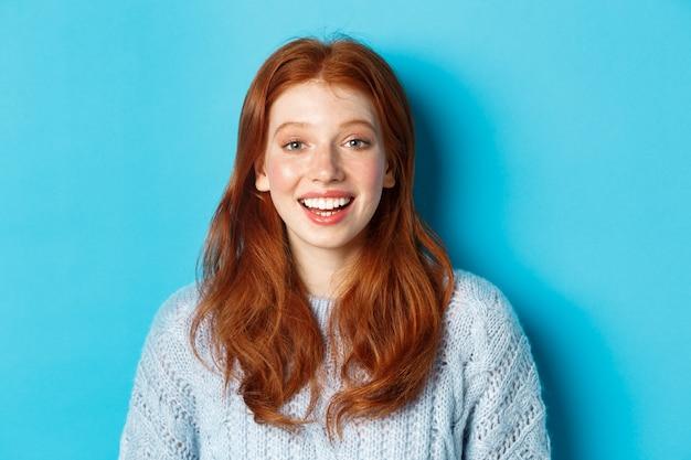 Primo piano di una ragazza rossa felice in maglione, che guarda l'obbiettivo con un sorriso speranzoso, in piedi su sfondo blu.