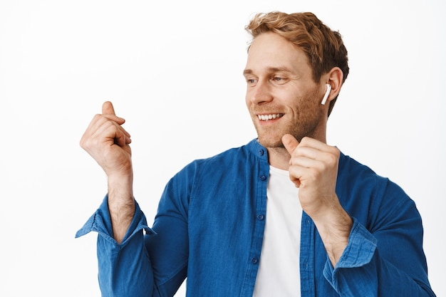 Close up of happy redhead guy dancing in wireless headphones, snap fingers and smiling pleased, listening music in earphones, standing over white wall
