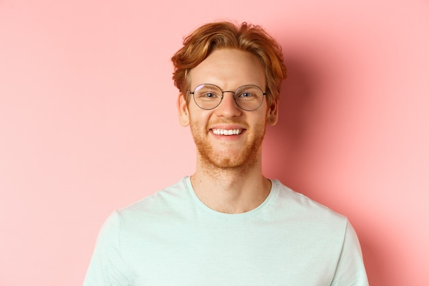 Close up of happy redhead man face, smiling with white teeth at camera, wearing glasses for better sight and t-shirt, standing over pink background.