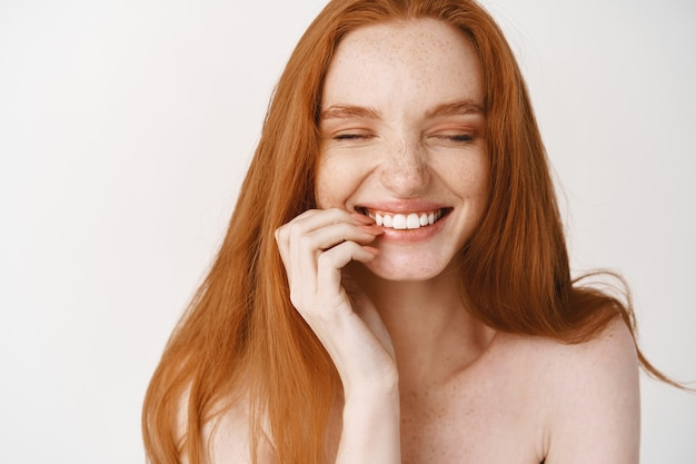 Close-up of happy redhead woman with pale no makeup skin and perfect smile, laughing and looking joyful, standing naked over white wall