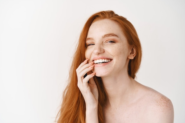 Close-up of happy redhead woman with pale perfect skin, laughing and showing white teeth, standing naked on studio wall