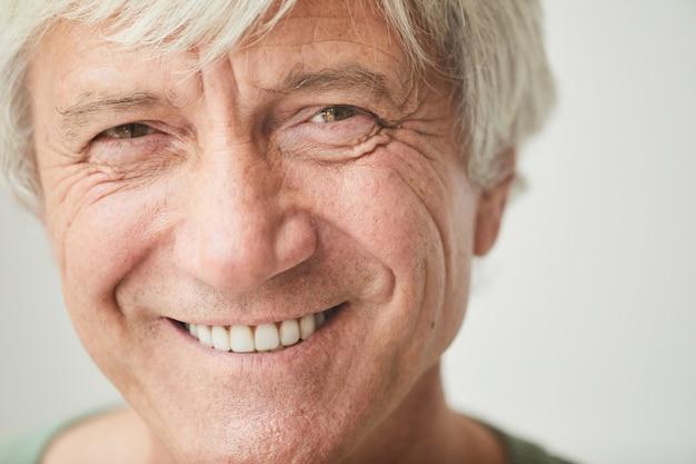 Close-up of happy senior man with white hair smiling at camera