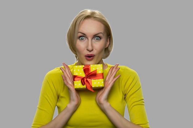선물 상자를 들고 행복 충격 된 여자를 닫습니다. 회색 바탕에 선물 상자를 들고 젊은 감정적 인 여자.