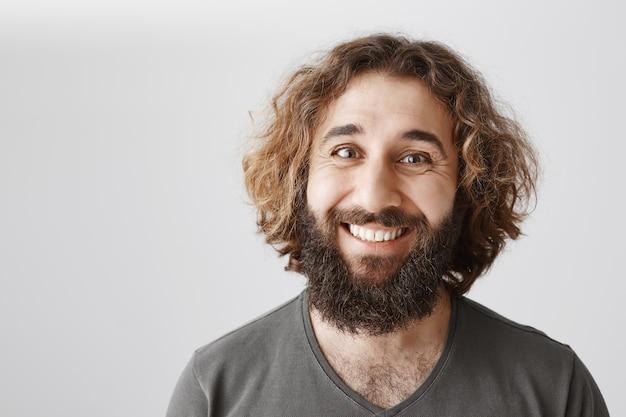 Primo piano di uomo mediorientale sorridente felice con barba lunga e acconciatura riccia