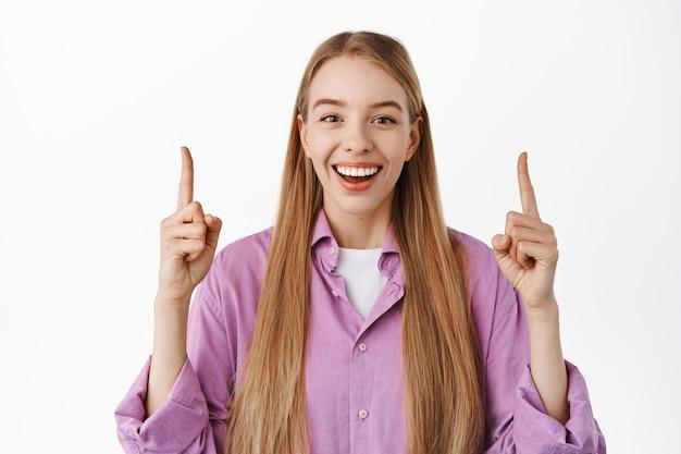 Primo piano di una donna sorridente felice che punta le dita in alto, ride e mostra pubblicità, in piedi in eleganti abiti casual contro il muro bianco