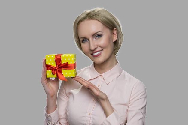 행복 한 웃는 여자 보여주는 선물 상자를 닫습니다. 회색 바탕에 작은 선물 상자를 들고 매력적인 비즈니스 아가씨.