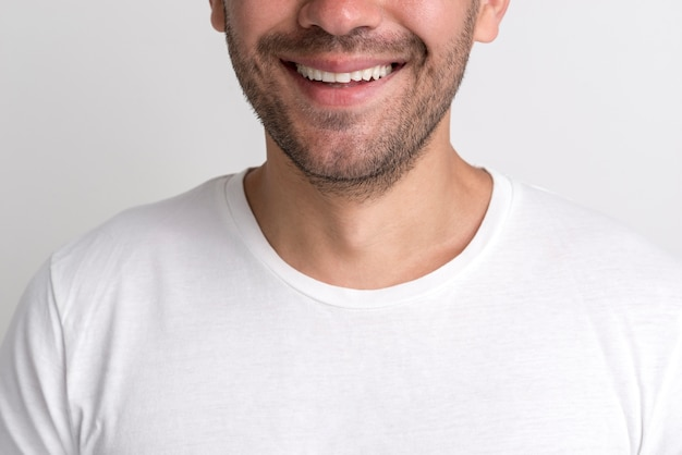 Close-up of happy stubble young man against white backdrop