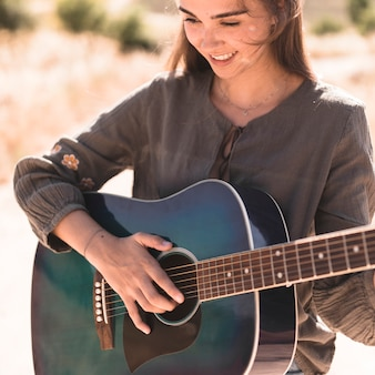 Close-up of a happy teenage girl playing guitar