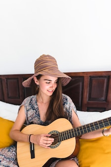 Close-up of a happy teenage sitting on bed playing guitar