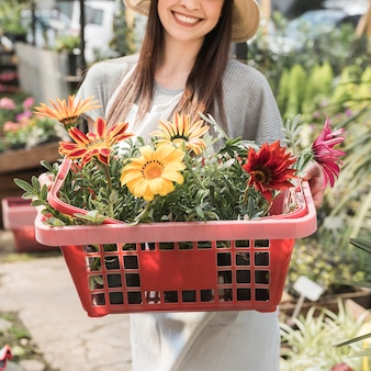 Close-up of a happy woman holding container with colorful flowers