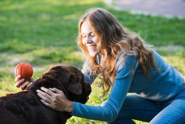 Close-up of a happy woman patting her dog in garden