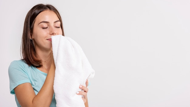 Close-up happy woman smelling clean towel