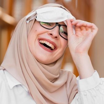 Макро счастливая женщина с медицинской маской
