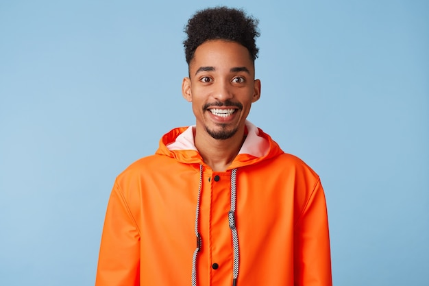Close up of happy young attractive african american dark skinned boy wears in orange rain coat, smiles broadly stands.