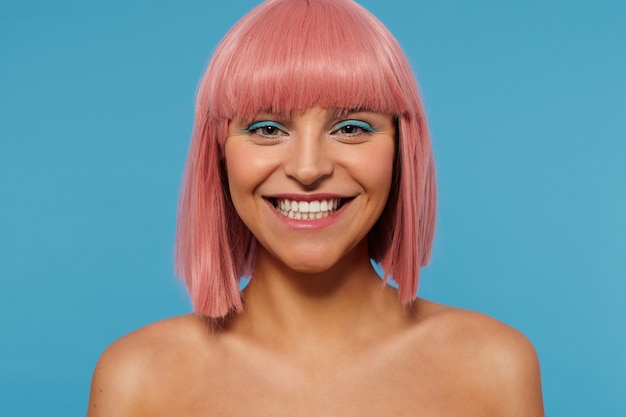Close-up of happy young attractive pink haired female with colored makeup showing her perfect white teeth while looking cheerfully at camera, isolated over blue background