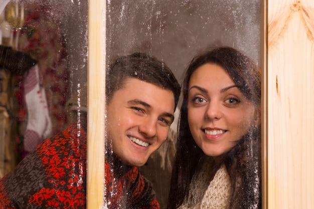 カメラを見ながらガラス窓の後ろに笑みを浮かべて冬のtシャツで幸せな若いカップルを閉じます。