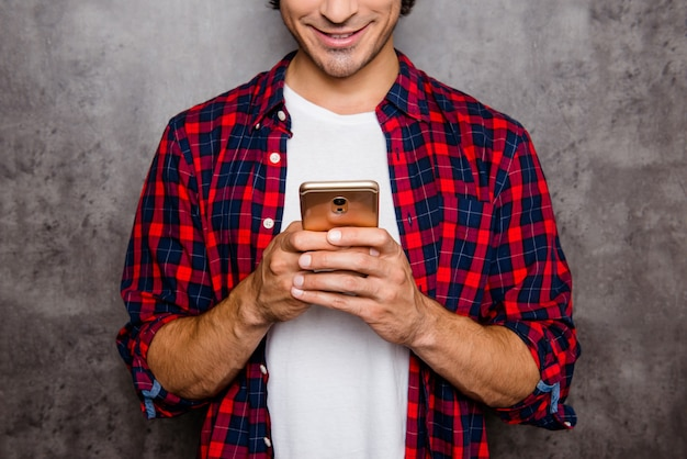 Close up of happy young man typing message on smartphone