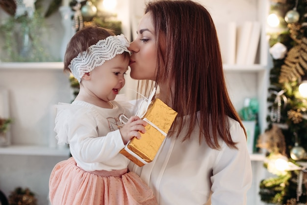 Close up happy young mother and cute daughter giving christmas gift and embracing. christmas holidays concept