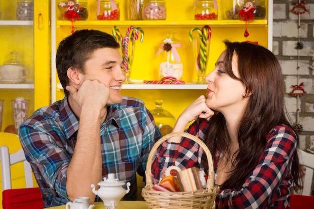 カフェでデートをしながら、顔に手を当ててお互いを見ているカジュアルな服装で幸せな若い白人カップルを閉じます。