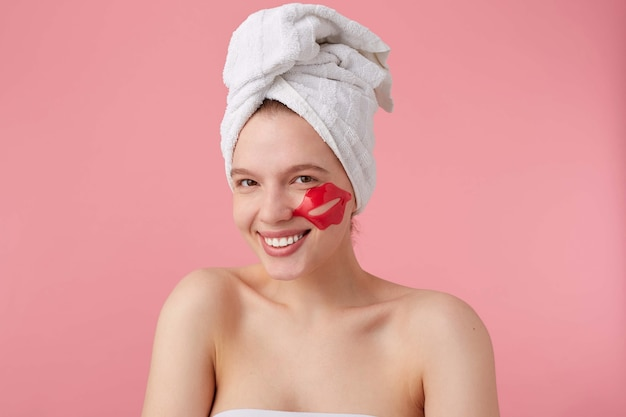 Close up of happy young woman after spa with a towel on her head, with patch for lips on cheeks, feels so happy, broadly smiles, stands.