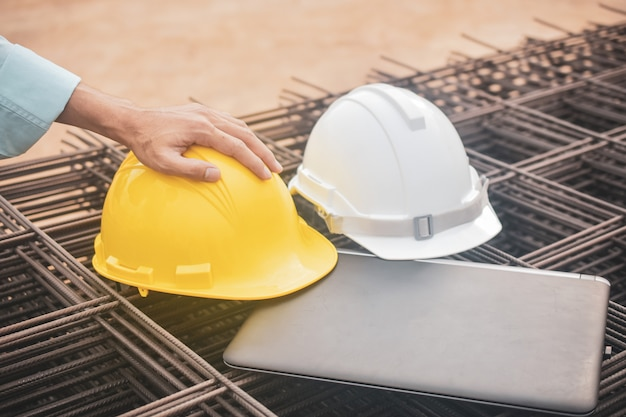 Close up hard hat on laptop at real estate construction site