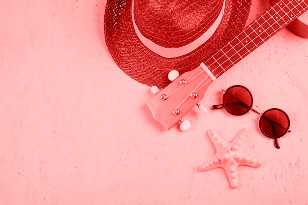 Close-up of hat; ukulele; sunglasses and starfish on coral textured background