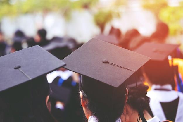 開始時に新卒者の帽子の若い女性の裏側のグループの群衆を閉じます。コンセプト教育おめでとうございます。大学での卒業式。ソフトフォーカス。