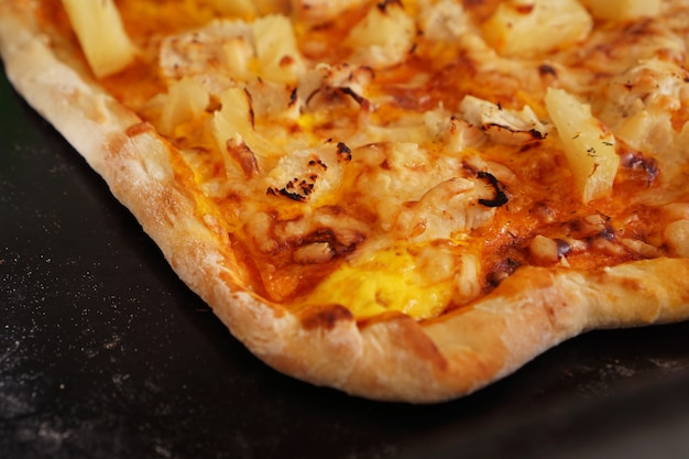 Крупным планом гавайская пицца - простая домашняя гавайская пицца на черном противне