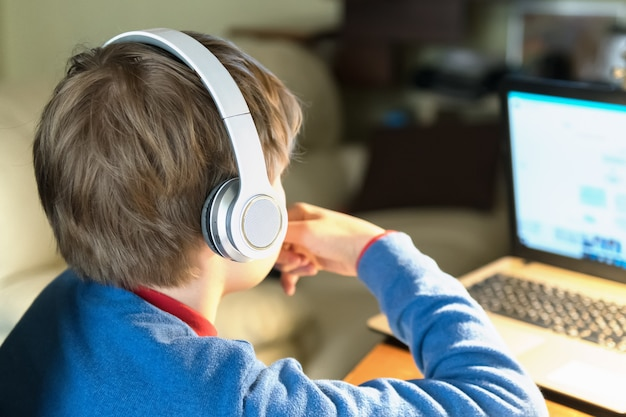 Close up of head of blond child boy in headphones sitting on the desk with notebook. homeschooling and education from home online