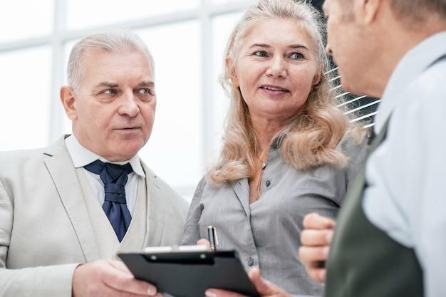 Закройте вверх. голова с помощниками обсуждает новый план работы. бизнес-концепция