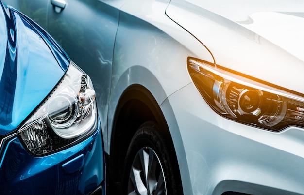 파란색과 흰색 suv 자동차의 전조등을 닫습니다. 파란 차는 흰색 차 옆에 주차되어 있습니다. 자동차 산업 개념. 전기 또는 하이브리드 자동 개념. 자동차 서비스. 도로 여행 모험. 자동차 렌탈.