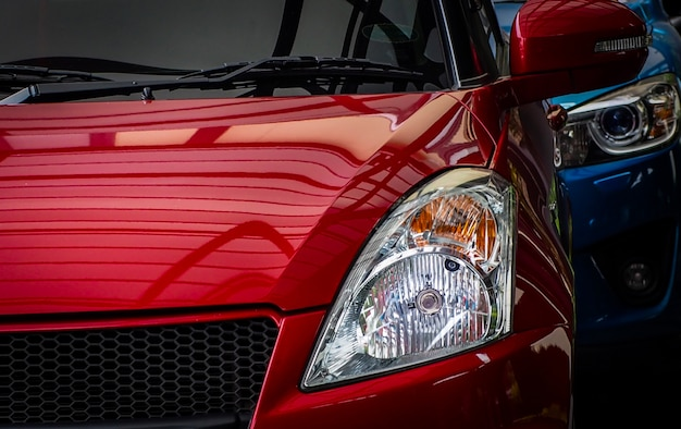 Close up headlamp light of red shiny suv car parked on concrete parking lot of the hotel or shopping mall