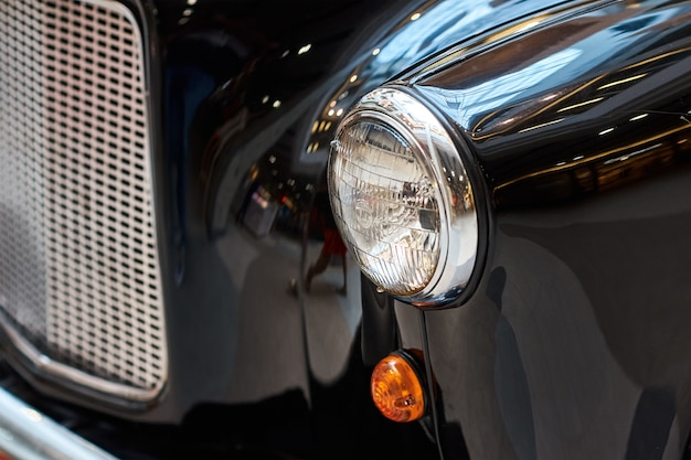 Close up headlight of a black vintage car