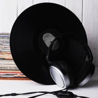 Close-up headphones near vinyl record with fingerprint