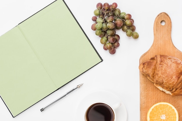 Close-up of healthy breakfast with coffee; notebook and pen on white backdrop