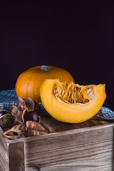 Close-up of a healthy chestnut and ripe pumpkin on wooden table